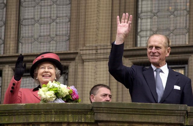 The Queen and the Duke of Edinburgh wave to crowds.