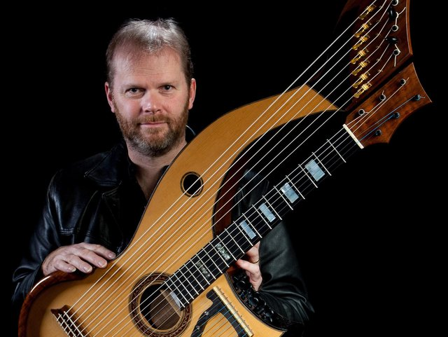 Jonathan Pickard with a harp-guitar which he has designed.