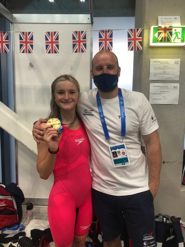 Abbie Wood shows off her second gold medal alongside coach Dave Hemmings in Budapest. She has two more individual events later this week.(Photo courtesy of Dave Hemmings)