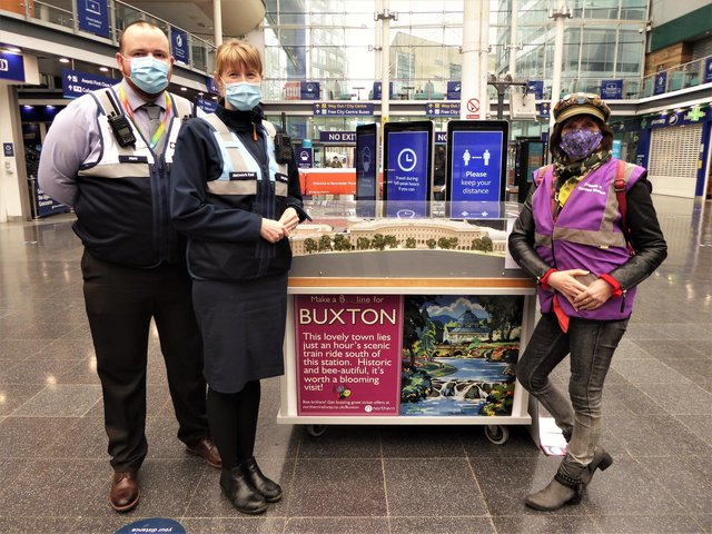 """The Kenneth Steel inspired """"bee-line to Buxton"""" travel poster and The Crescent hotel and spa buildings model on the main concourse at Manchester Piccadilly Station flanked by (from left) Matthew Jump, Piccadilly's Deputy Station Manager, Margaret Edge, Piccadilly's Station Control Manager and Sue Mellor, Secretary, Friends of Buxton Station."""