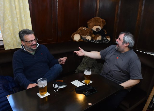 Two customers enjoy a drink at The Queens Head. (Photo by Nathan Stirk/Getty Images)