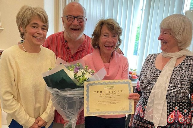 Christine, third from left, receives a certificate to commemorate her 25th anniversary as a Samaritan from fellow volunteers Deborah, Julian and Maggie.