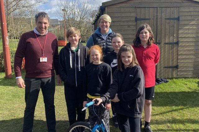 Some of the children at Hayfield Primary School with their headteacher Stefan Papadopoulos and PE Teacher Zoe Shaw, with a bike currently under repair and renewal.