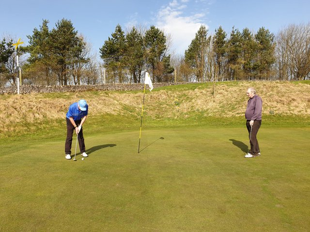 Alan Dickman putting at the fifth hole as Ken Lomas looks on.