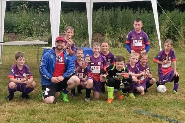 The successful Buxton Broncos side with their trophy.