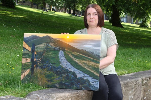Helen Homer with one of her late husband's images which she is selling to raise money for Buxton Mountain Rescue Team