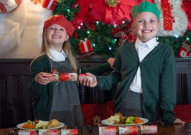 Ivy Dakin, 5, and Mia Dakin, 7, pull crackers.