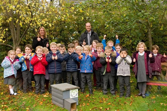 Whaley Bridge Primary school class accepting hedgehog house from Biodiversity Whaley group.